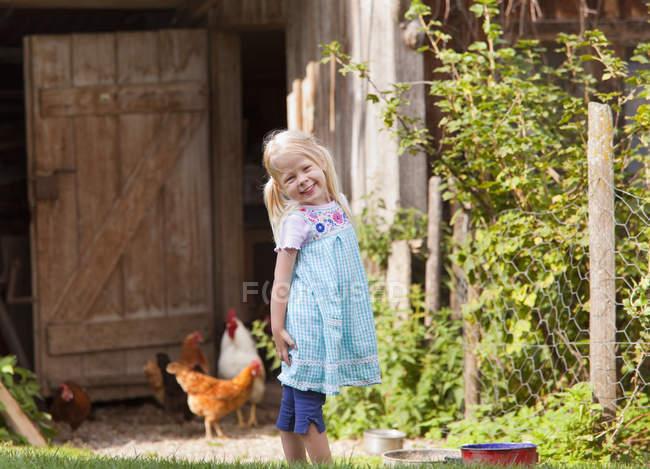 Menina bonito pouco com frango na fazenda — Fotografia de Stock