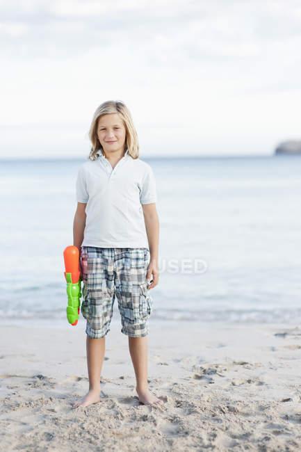Хлопчик з водяної гармати стоячи на пляжі — стокове фото