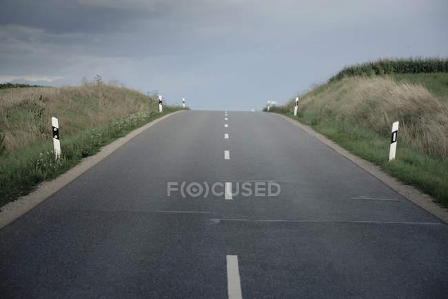 Германия, Ингольштадт, пустые проселочной дороге с пасмурное небо — стоковое фото