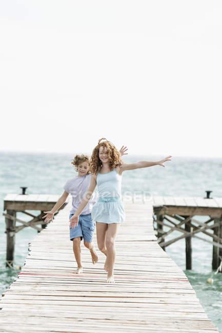 Дівчинка і хлопчик, що працюють на пристані на морі — стокове фото