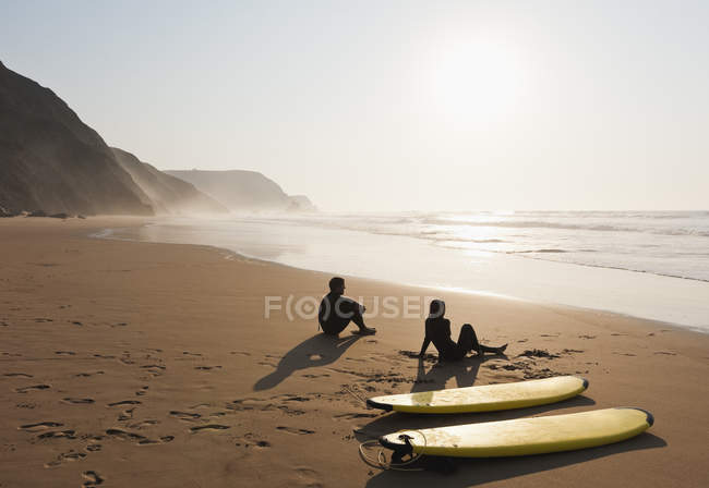 Couple sitting on beach with surfboards — Stock Photo