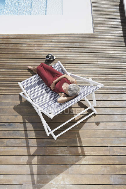 Senior woman relaxing on deck chair — Stock Photo