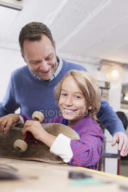 Батько і син ремонту скейтборд — стокове фото