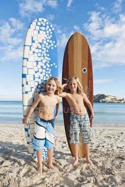 Дети, стоя с доски для серфинга — стоковое фото