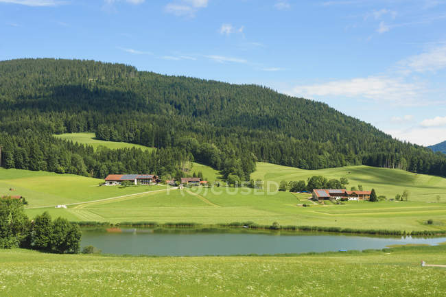 Distant view of village houses with alps at daytime, Bavaria, Germany, — Stock Photo
