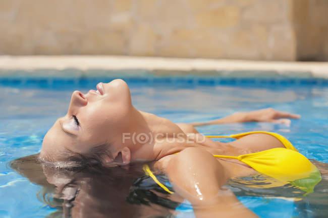 Young woman enjoying bath in swimming pool — Stock Photo