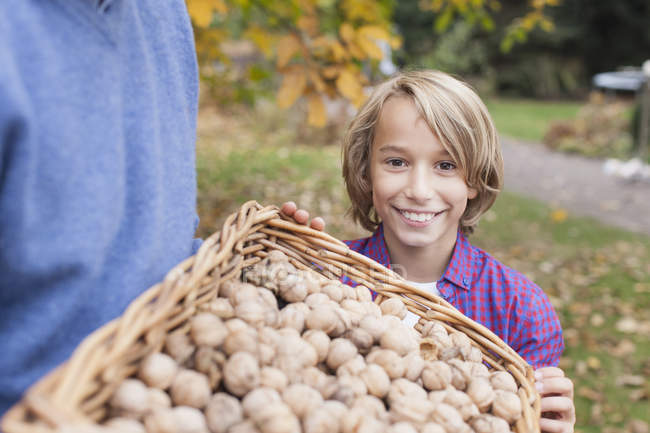 Boy holding crate of potatoes — Stock Photo