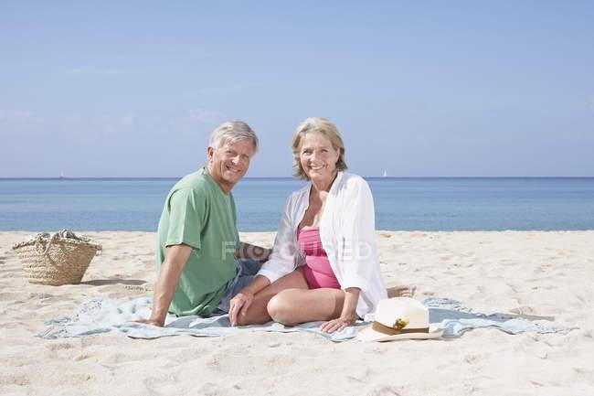 Пожилые супружеские пары, сидя на песчаный пляж — стоковое фото