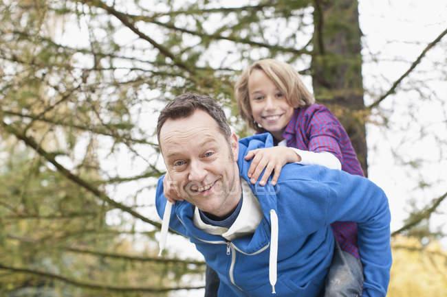 Батько, даючи piggyback поїздка до сина — стокове фото