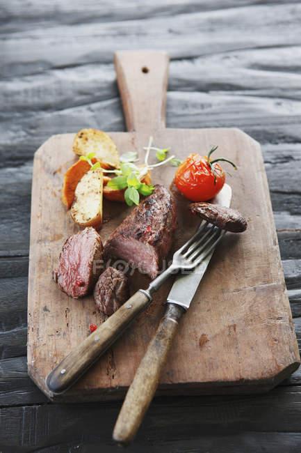 Ternera con vegetales en tajadera con tenedor y cuchillo - foto de stock