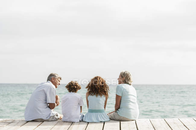 Grandparents with grandchildren sitting on jetty — Stock Photo