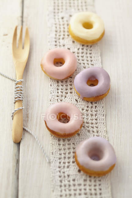 Glazed baked doughnuts with wooden fork on table — Stock Photo