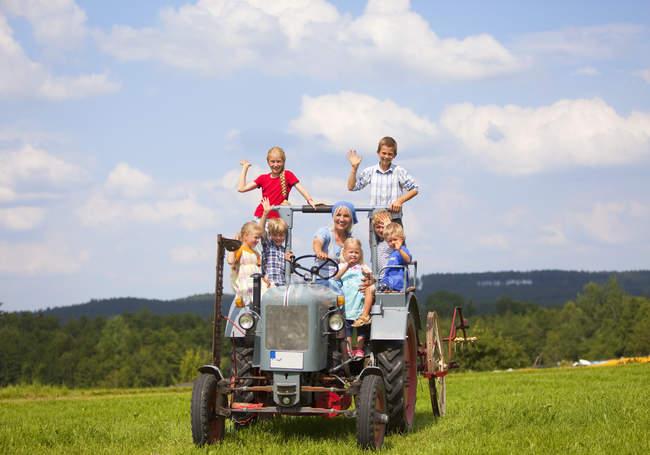 Donna con un gruppo di bambini che si siedono in vecchio trattore — Foto stock