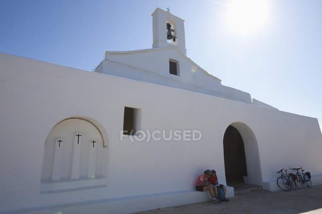 Spanien, Ibiza, reifer Mann und Mitte Erwachsene Frau sitzt vor der Kirche — Stockfoto