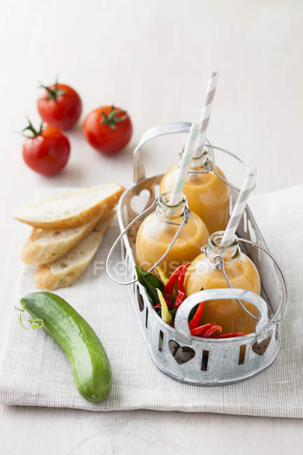 Bottles of gazpacho with chillies, bread and tomatoes on napkin — Stock Photo