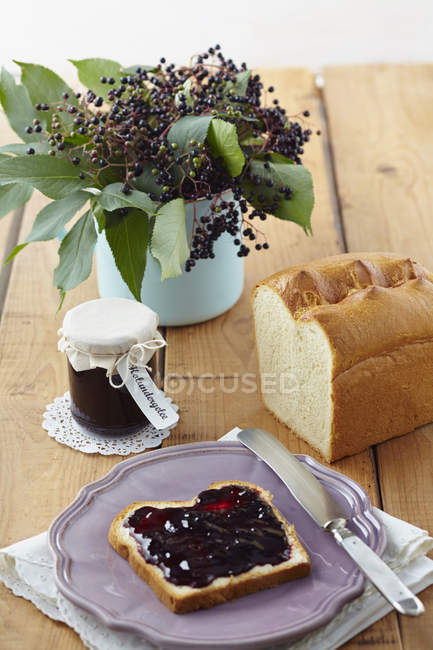 Elderberry jam with white bread on wooden table — Stock Photo