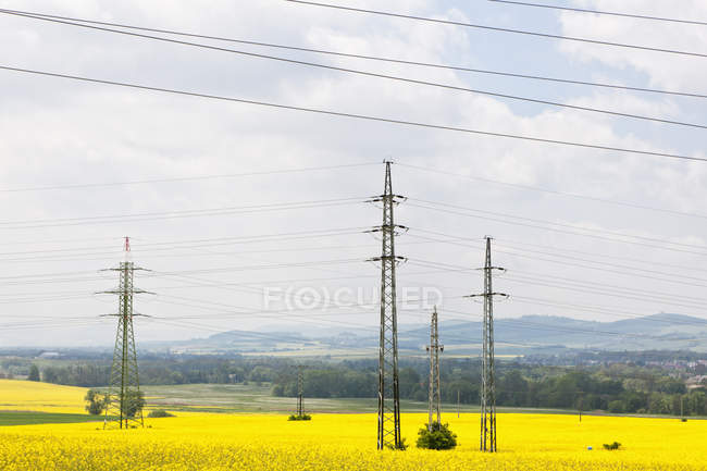 View of electricity pylons in rapeseed field, Germany, Bavaria, — Stock Photo