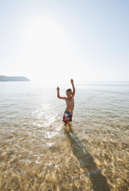 Португалия, мальчик стоял в воде на пляже — стоковое фото