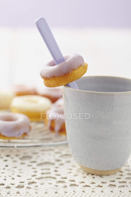 Glazed baked doughnuts with cup placed on white cloth, close-up — Stock Photo