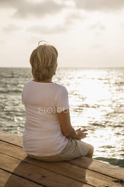 Donna anziana seduta sul molo — Foto stock