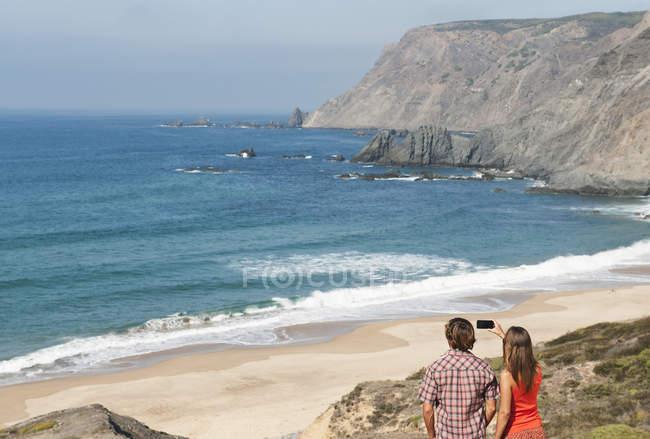 Пара фотографировать на пляже — стоковое фото