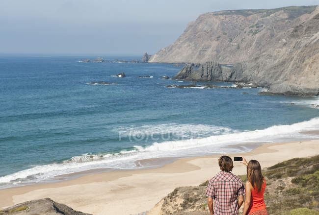 Couple taking photograph at beach — Stock Photo