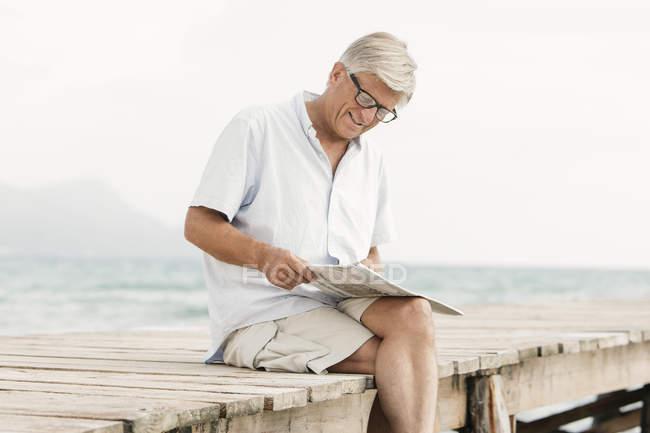 Старший читает газету на пристани — стоковое фото