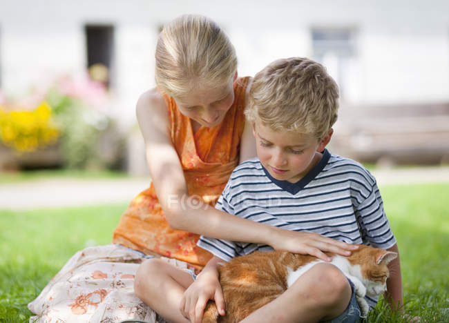 Boy and girl with cat on farm — Stock Photo