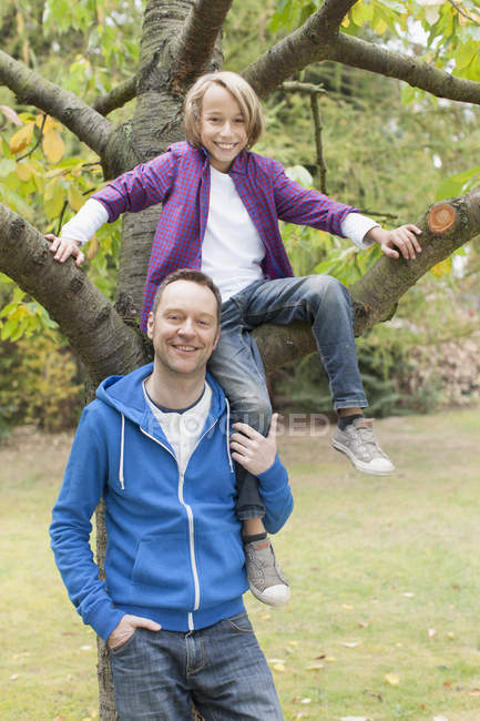 Father standing next son sitting on tree — Stock Photo