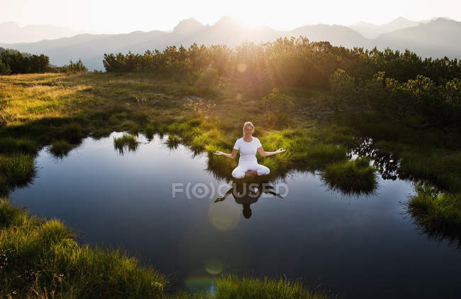 Austria, Salzburg County, Young woman sitting near mountain lake and doing meditation — Stock Photo