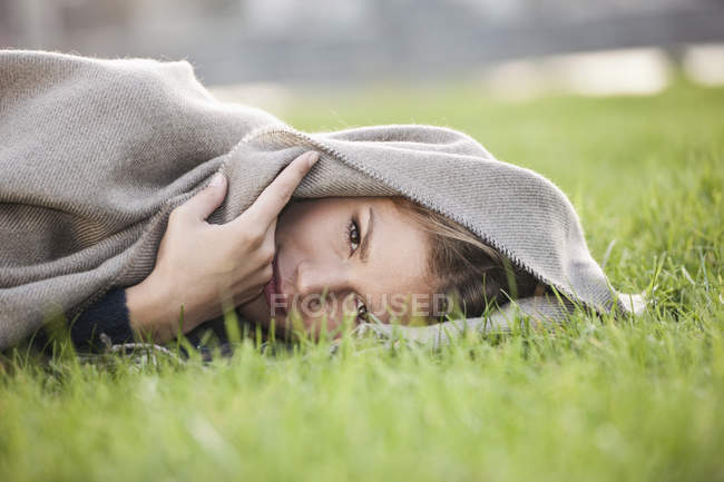 Portrait of Young woman lying in grass — Stock Photo