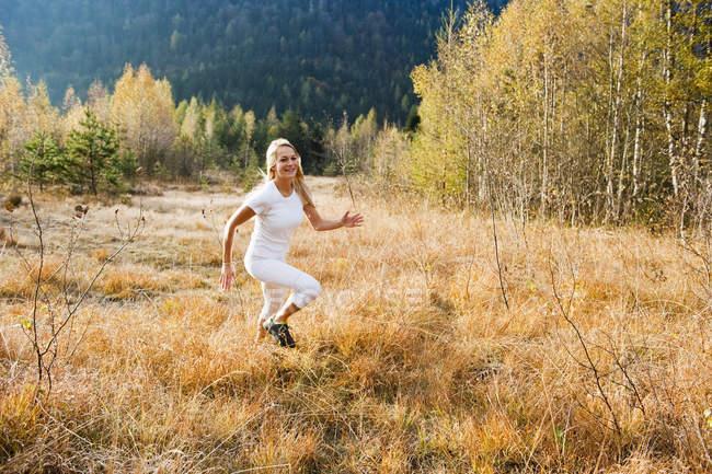Австрия, Озил, Молодая женщина, бегущая осенью — стоковое фото