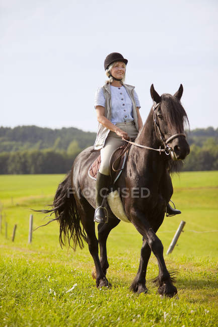 Mature woman riding horse — Stock Photo