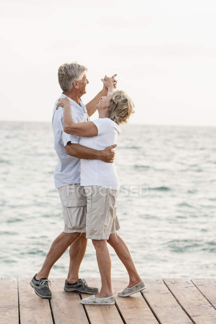Senior couple dancing on jetty at the sea — Stock Photo