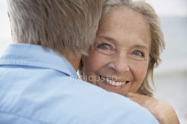 Senior woman embracing husband — Stock Photo