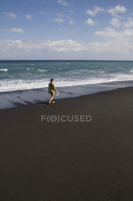 Молодая женщина, ходить на черном песке — стоковое фото