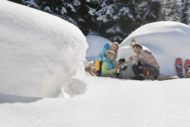 Семья, пить чай вблизи иглу в Зальцбурге, Австрия — стоковое фото