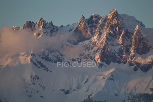 Austria, Tirol, Kitzbuhel, montañas cubiertas de nieve de Wilder Kaiser en la madrugada - foto de stock