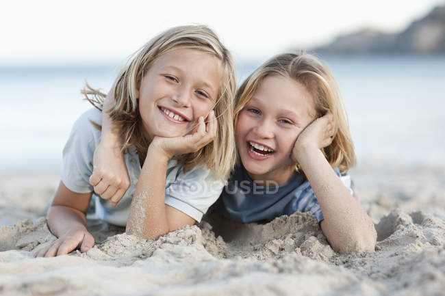 Children lying in sand on beach — Stock Photo
