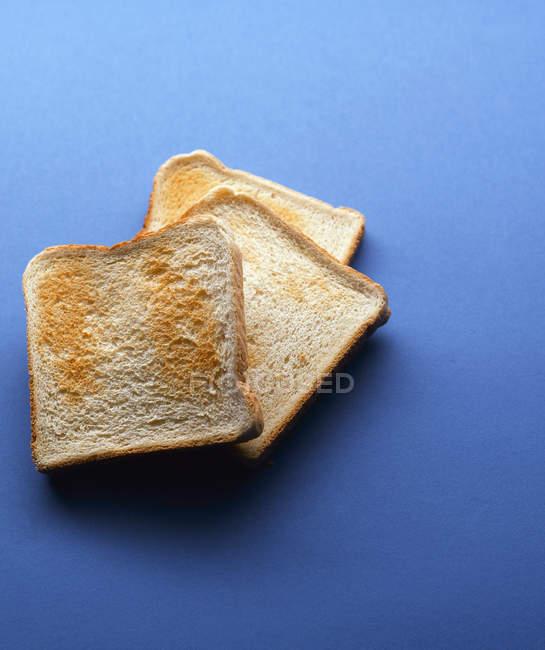 Rebanadas de pan tostado sobre fondo azul - foto de stock