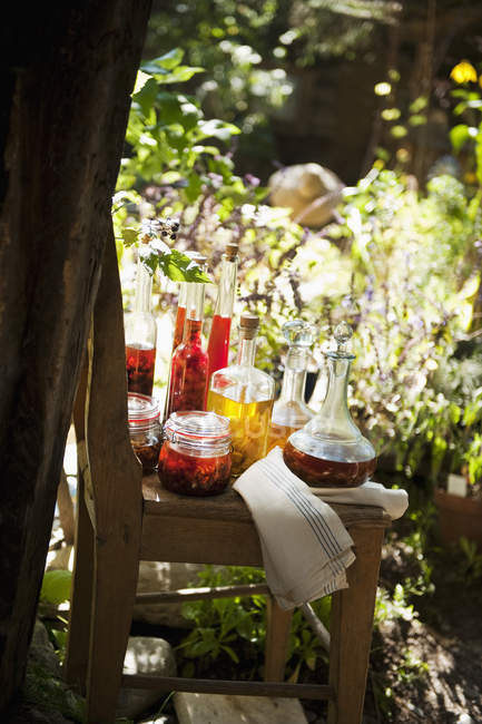 Various herbal oils on chair in countryside garden — Stock Photo