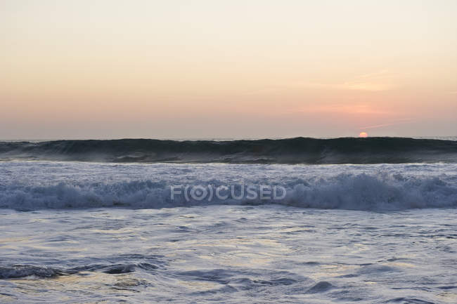 Portugal, Algarve, Sagres, View of Atlantic ocean with breaking waves at sunset — Stock Photo