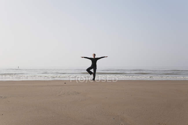 Belgium, Young woman standing in tree pose at North Sea — Stock Photo