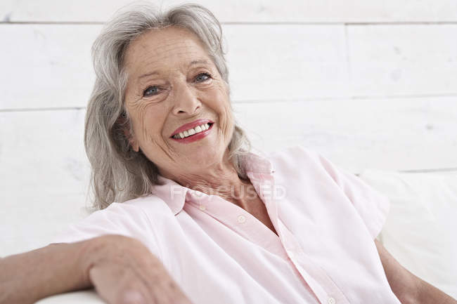 Woman sitting on couch and looking at camera — Stock Photo