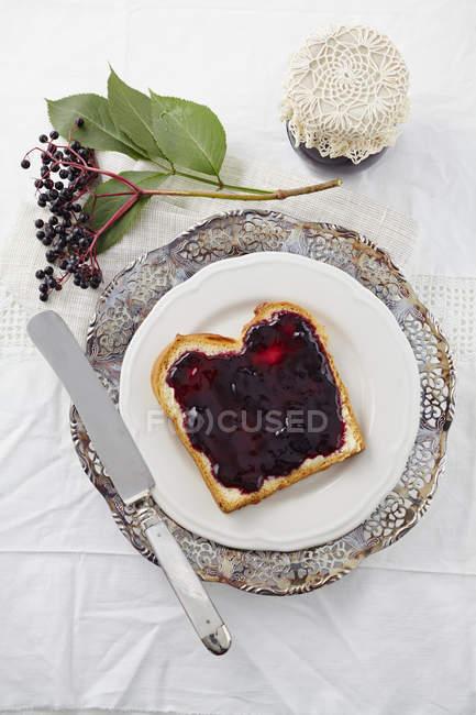 Elderberry jam with white bread on plate — Stock Photo
