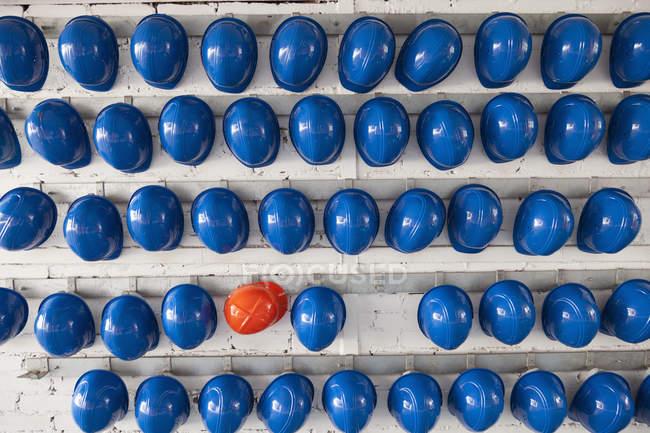 Reihen blauer und orangefarbener Schutzhelme im Regal — Stockfoto