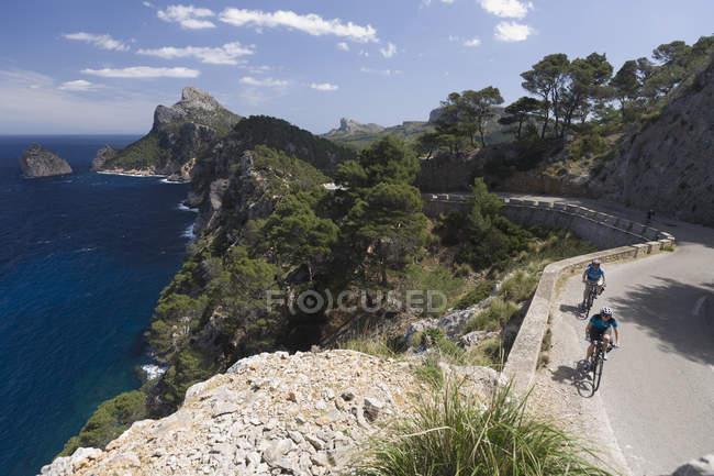 Spagna, Maiorca, Uomo e donna in bicicletta su strada a Cap de Formento — Foto stock