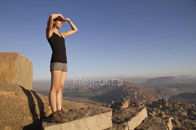 India, Karnataka, Hampi, Young woman walking on rock — Stock Photo