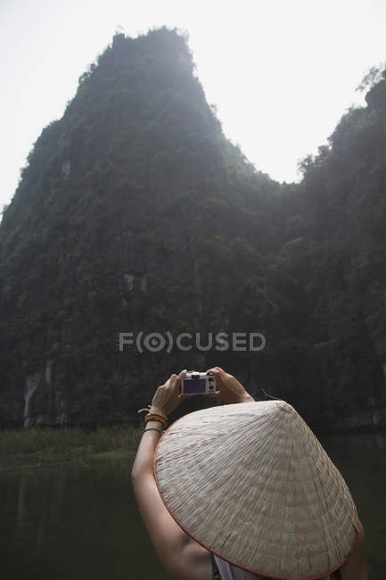 Vietnam, Ninh Binh, Young tourist taking photograph of landscape — Stock Photo