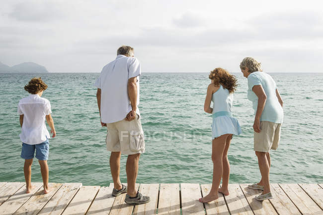 Grandparents with grandchildren standing on jetty — Stock Photo